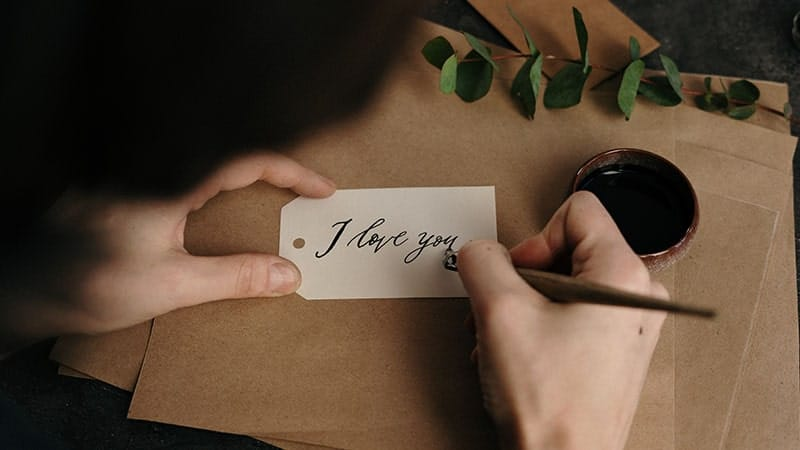 kata-kata indah cinta - pria menulis i love you di kertas